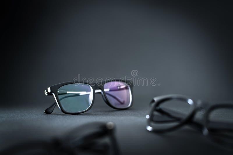 Новые eyeglasses и различные спецификации на таблице стоковые изображения rf