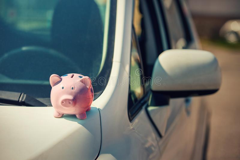 Новый автомобиль с розовым piggy банком денег на клобуке Экономический успех, страхование собственности стоковое изображение rf
