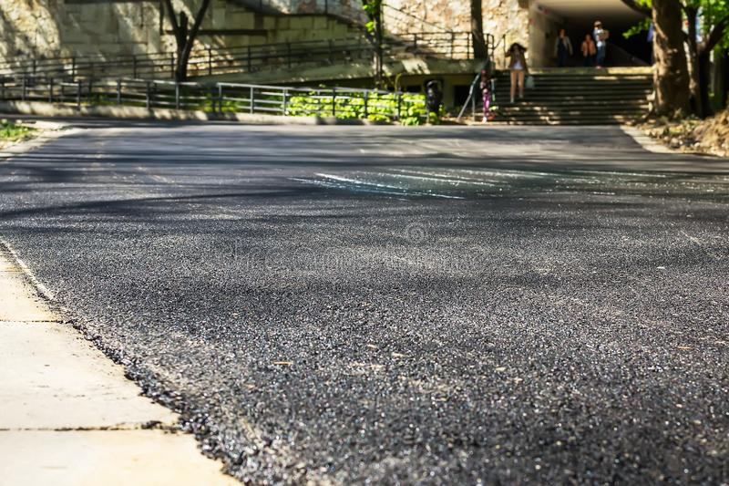 Новый асфальт на дороге в общественном парке Ремонт дорог асфальта Заасфальтируйте вымощать и городское улучшение стоковое изображение