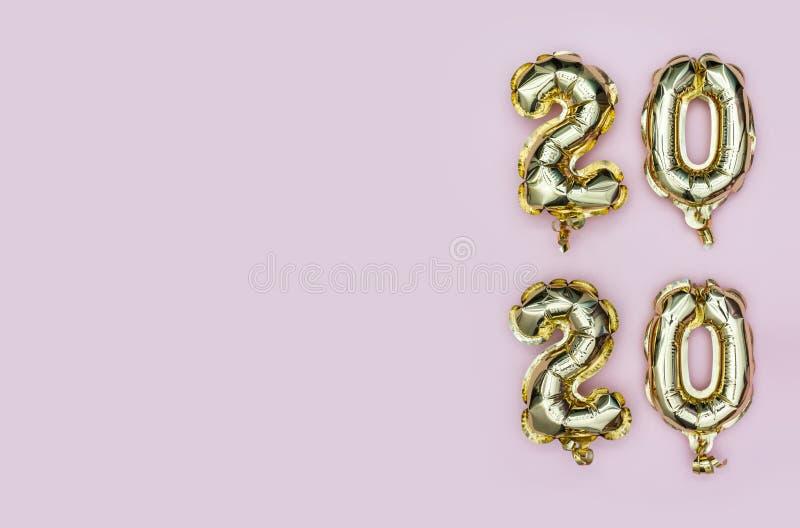 Новый год 2020 Вертикальная композиция шариков золотой фольги № 2020 на пастельном розовом фоне Плоский рисунок с копировальным п стоковая фотография