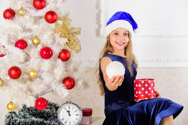 Новый Год принципиальной схемы счастливое Девушка ребенк сидит около подарочной коробки владением рождественской елки Шляпа santa стоковое изображение rf