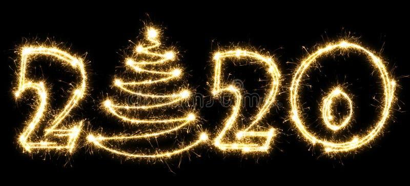 Новый 2020 год с рождественской елкой, сделанной спарклером Номер 2020 и подписывать написанные сверкающие зажигалки Изолировано  стоковые фото