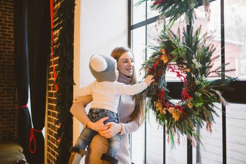 Новый Год темы и мама праздников рождества кавказская держат сына в ее оружиях на 1 год дома в интерьере просторной квартиры окол стоковые изображения