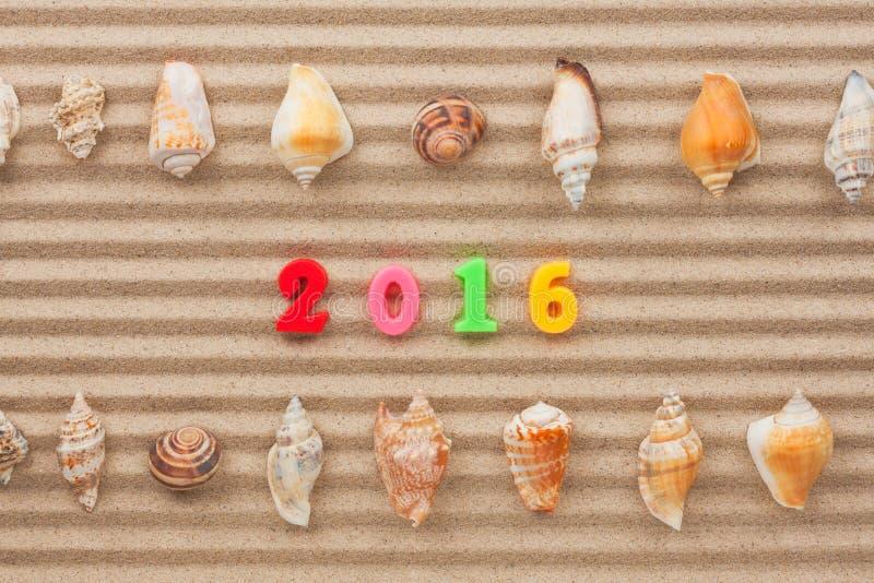 Новый Год 2016 написанный в песке и раковине стоковые изображения