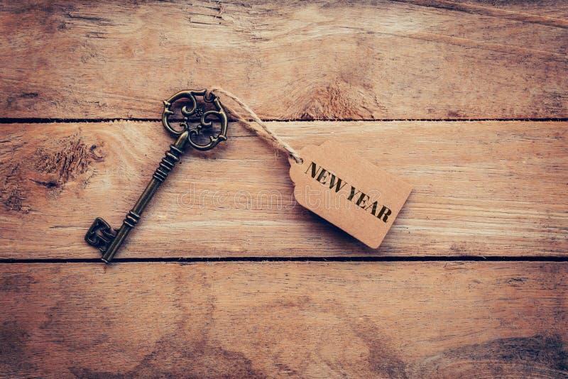 Новый Год на бирке с ключом на деревянной предпосылке таблицы стоковое фото