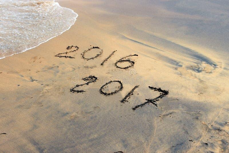 Новый Год 2017 приходя концепция - надпись 2016 и 2017 на песке пляжа стоковые фотографии rf
