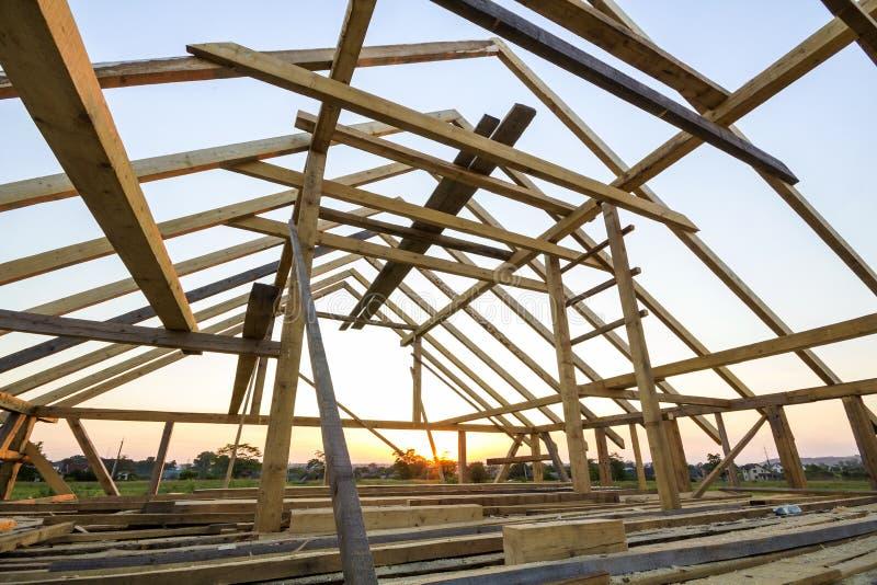 Новый деревянный дом под конструкцией Конец-вверх рамки крыши чердака против ясного неба from inside Экологический дом мечты есте стоковое фото rf