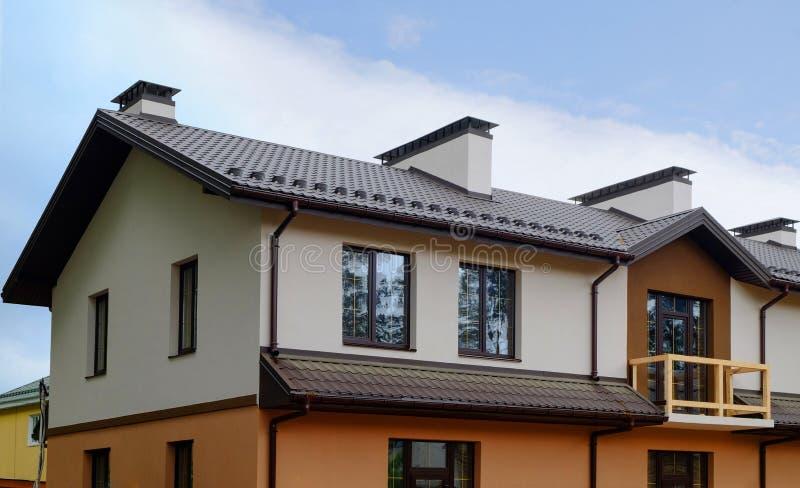 Новый дом коттеджа с крышей металла, сточной канавой дождя и балконом Печная труба и система вентиляции стоковые изображения rf