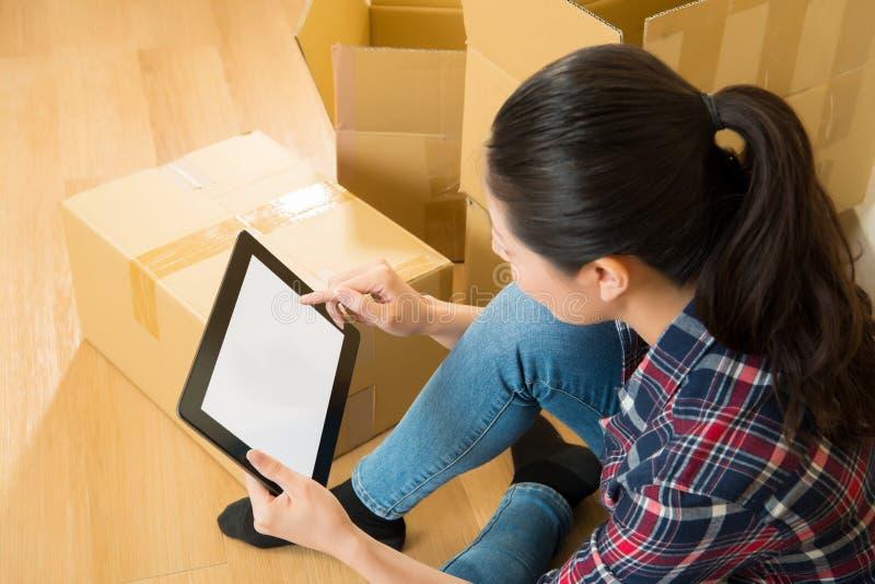 Новый дом женщины moving проверяя на цифровой таблетке стоковое фото rf