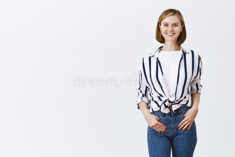 Новый работник начиная работу в офисе, усмехаясь пока встречающ сотрудников Очаровательная счастливая молодая женщина в ультрамод стоковые изображения rf