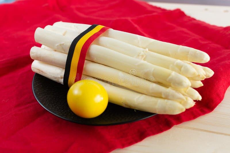 Новый сбор белой спаржи, высококачественной бельгийской спаржи с лентой в цветах бельгийского флага стоковые фото