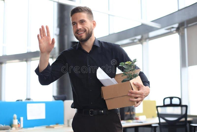 Новый сотрудник в современном большом офисе носит коробку с документами и бумагами для работы стоковое изображение rf