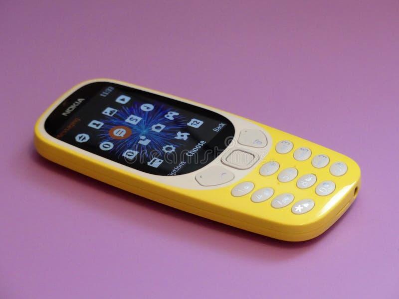 Новый телефон особенности Nokia 3310 выдал в 2017 на розовой предпосылке стоковые фото