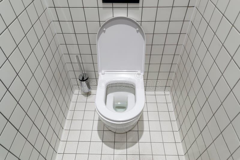 Новый чистый туалет, с современным дизайном и белым керамическим шаром туалета против светлых плиток стоковые фотографии rf