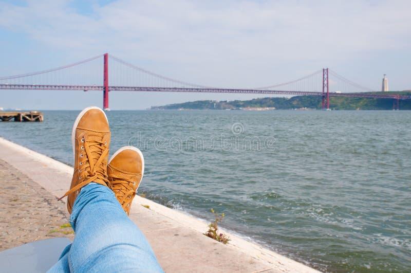Download Нога ботинки около отдыхая воды Взгляд моста Лиссабона красный на предпосылке Стоковое Фото - изображение насчитывающей vintage, ботинок: 40585648