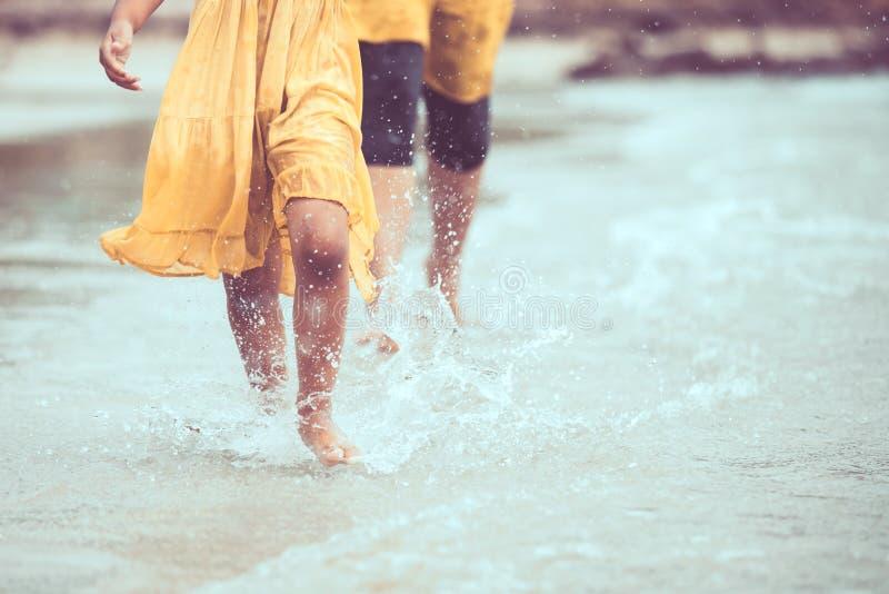 Нога девушки маленького ребенка бежать на пляже с брызгать воды стоковое изображение