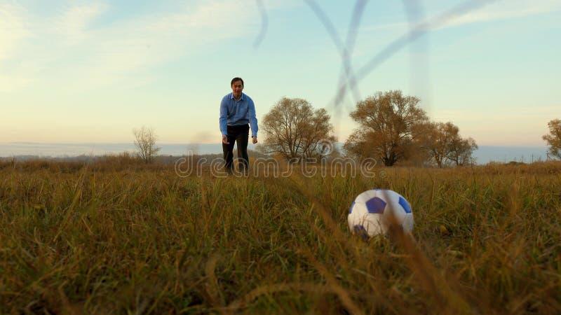 Нога девушки ударяет шарик задвижек человека футбольного мяча семья играет футбол в парке шарик игры папы и дочери на поле стоковые изображения rf