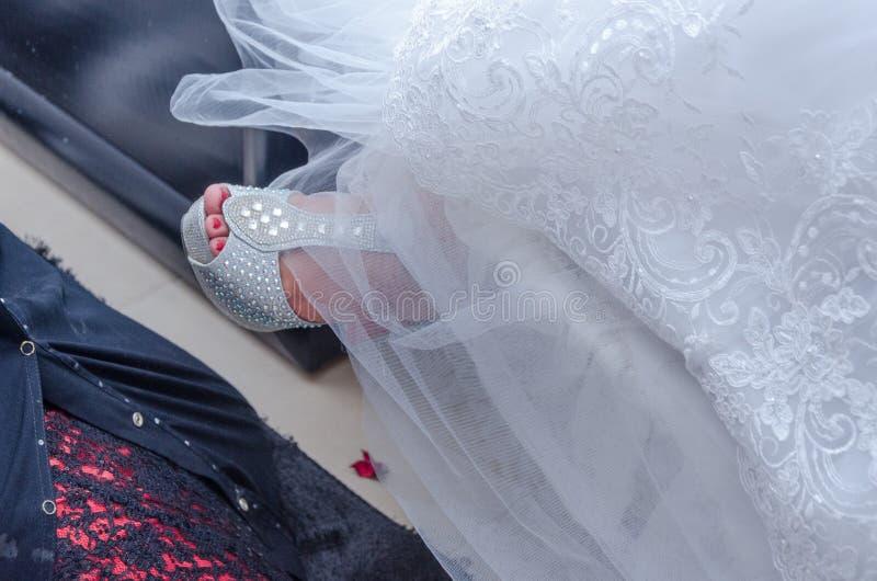 Нога невесты в белые сандалии и часть платья свадьбы стоковые изображения rf