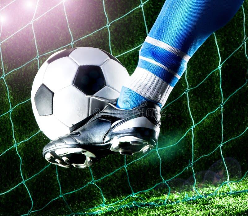 Нога пиная футбольный мяч стоковые фотографии rf