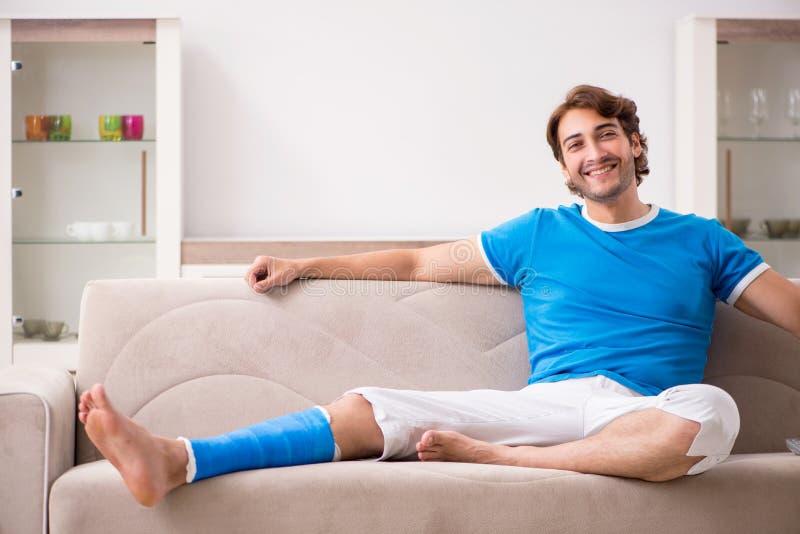 Нога повредила молодого человека на софе стоковое изображение