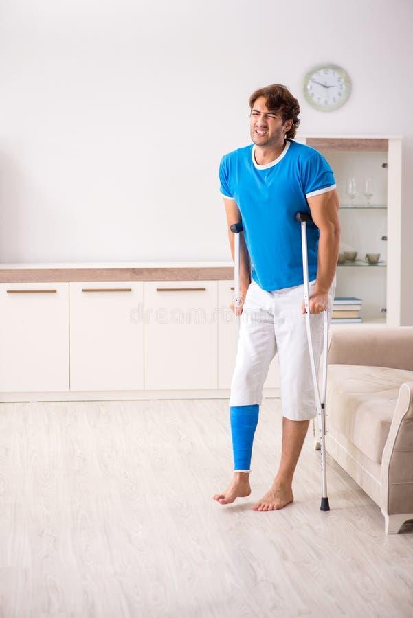 Нога повредила молодого человека с костылями дома стоковые изображения