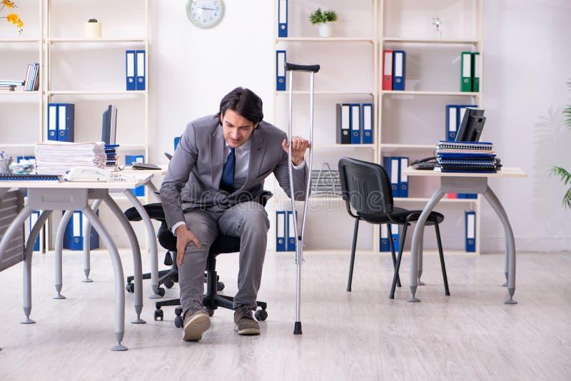 Нога повредила мужского работника работая в офисе стоковое изображение