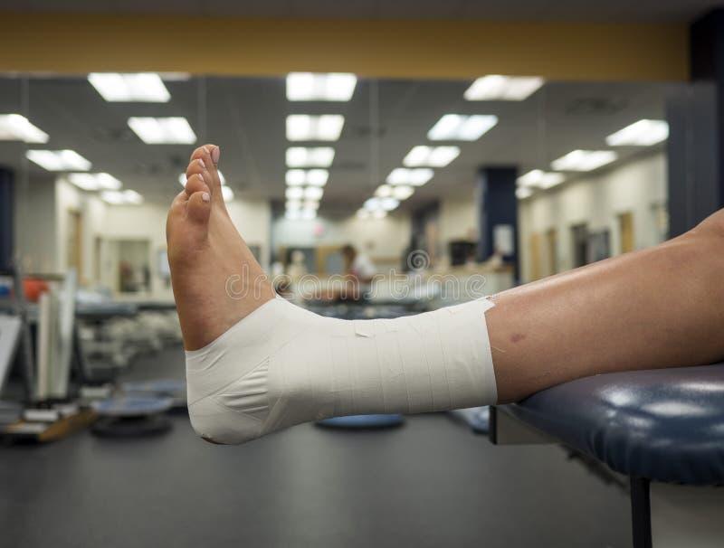 Нога ` s спортсмена с работой ленты лодыжки для поддержки вися с таблицы в медицинской клинике стоковые фото