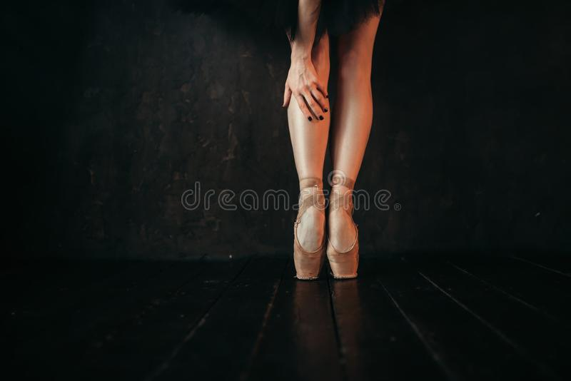 Ноги артиста балета в pointes, черном деревянном поле стоковое изображение