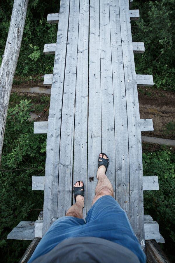 Ноги взгляд сверху в темповых сальто сальто на узком деревянном мосте над рекой стоковое изображение