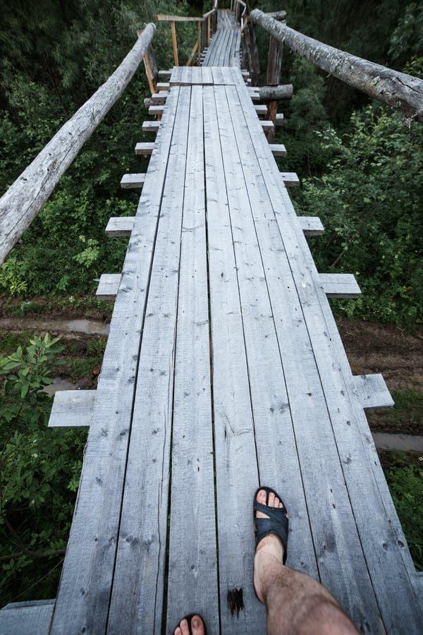 Ноги взгляд сверху в темповых сальто сальто на узком деревянном мосте над рекой стоковое изображение rf
