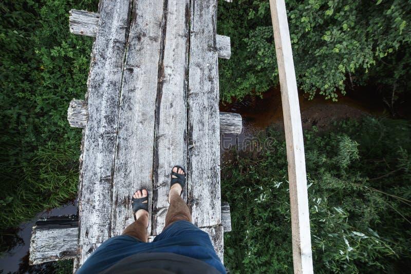 Ноги взгляд сверху в темповых сальто сальто на узком деревянном мосте над рекой стоковые фотографии rf