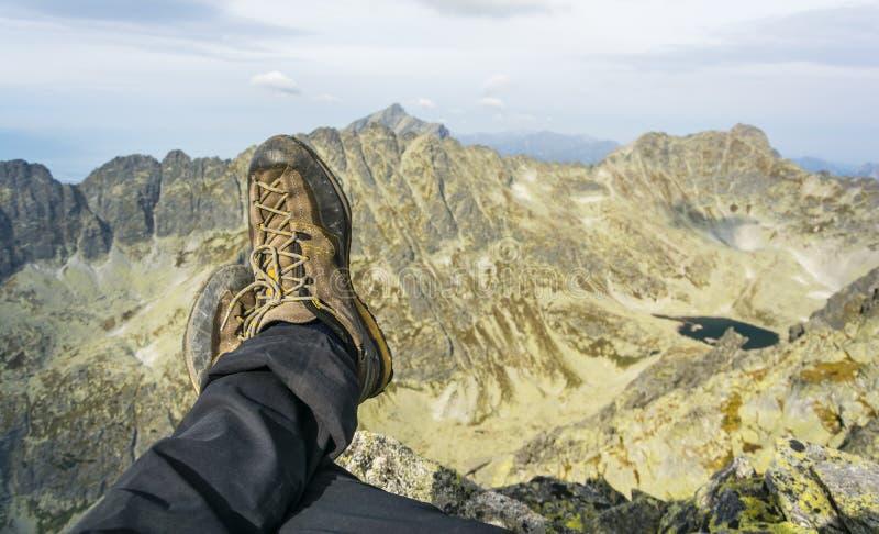 Ноги высокогорного туриста с ботинками на предпосылке гор стоковая фотография
