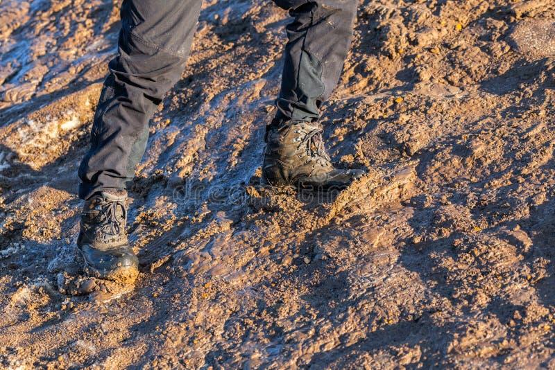Ноги в серых брюках и ботинках трека вверх на грязном холме на выравнивать солнечный свет стоковое изображение