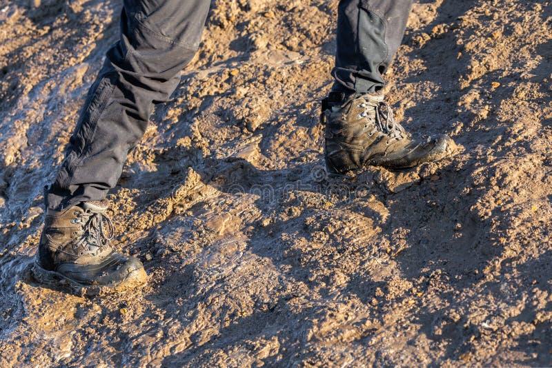 Ноги в серых брюках и ботинках трека вверх на грязном холме на выравнивать солнечный свет стоковое изображение rf