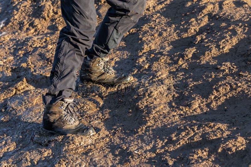 Ноги в серых брюках и ботинках трека вверх на грязном холме на выравнивать солнечный свет стоковые фотографии rf