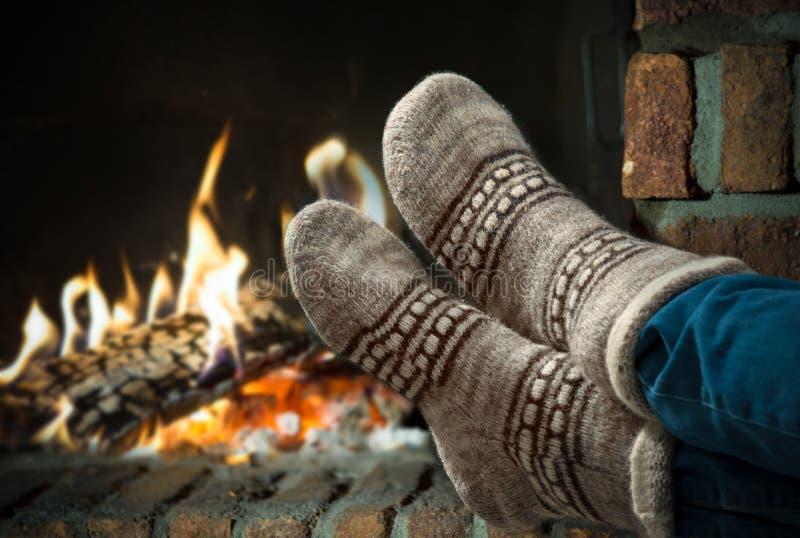 Ноги в шерстях socks греть на камине стоковая фотография rf