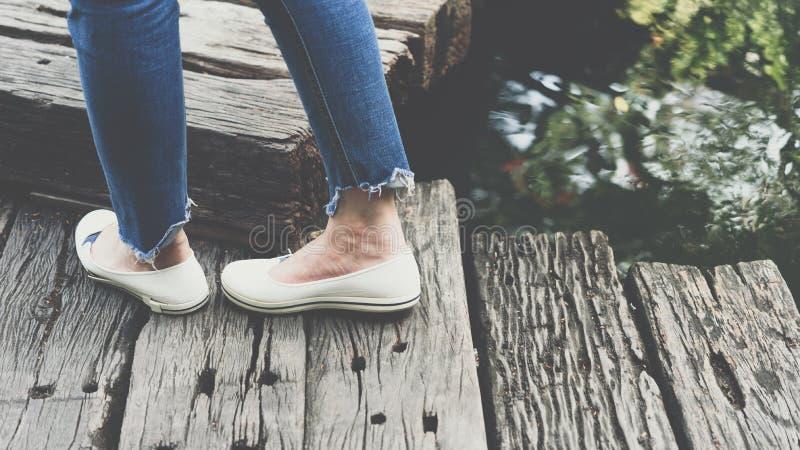 Ноги голубых джинсов одежды женщин и белых ботинок стоковые изображения