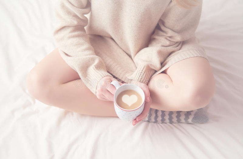 Ноги девушки греют шерстяные носки и чашку кофе грея, утро зимы в кровати стоковое изображение
