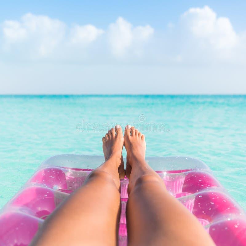 Ноги девушки летнего отпуска загорая ослабляя в океане стоковое фото