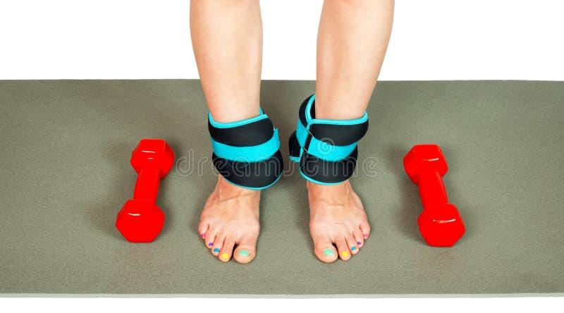Ноги девушки при изолированные весы и гантели лодыжки, стоковое фото