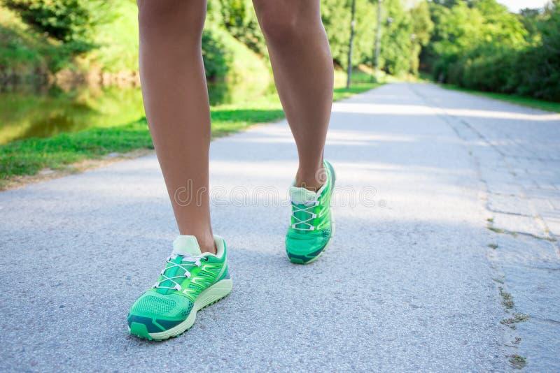 Ноги женщины бегуна бежать на дороге в парке стоковые изображения rf