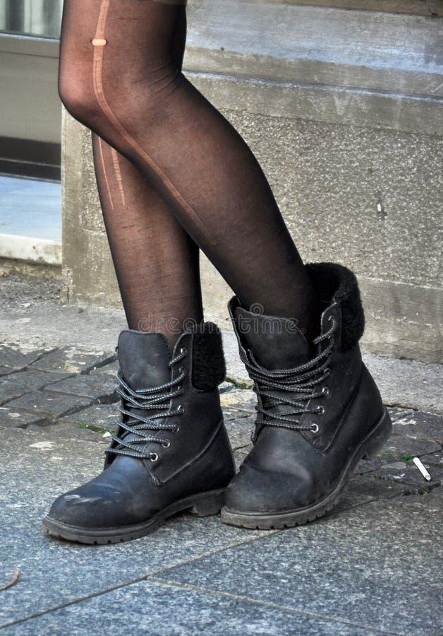Черные ботинки весны и сорванные чулки стоковые фотографии rf