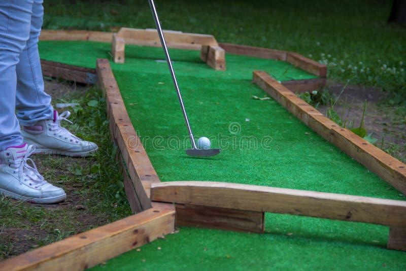 Ноги женщины, играя в гольф на зеленом цвете, женщина кладя шарик Окончательная съемка, гольф стоковые изображения rf
