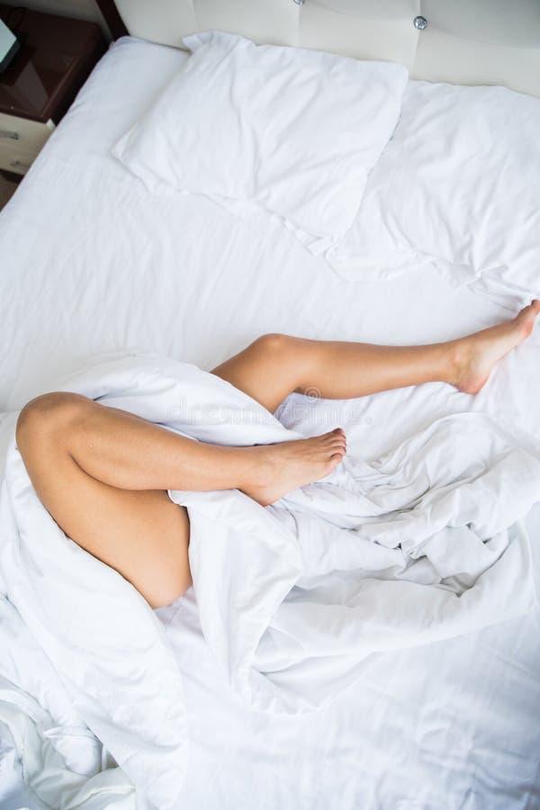 Ноги женщины на кровати стоковые изображения rf