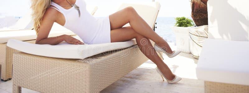 Ноги женщины на lounger солнца стоковая фотография rf