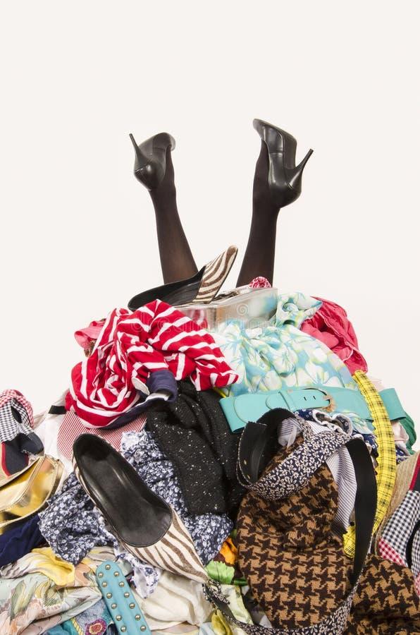 Ноги женщины достигая вне от большой кучи одежд и аксессуаров стоковое фото rf