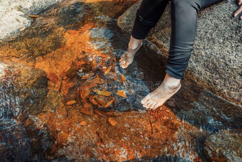 Ноги женщин в водопаде, ослабляют концепцию перемещения в лесе стоковые фотографии rf