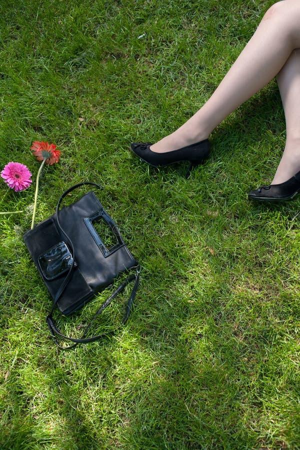 Ноги женщин отдыхая на зеленой траве стоковое изображение rf