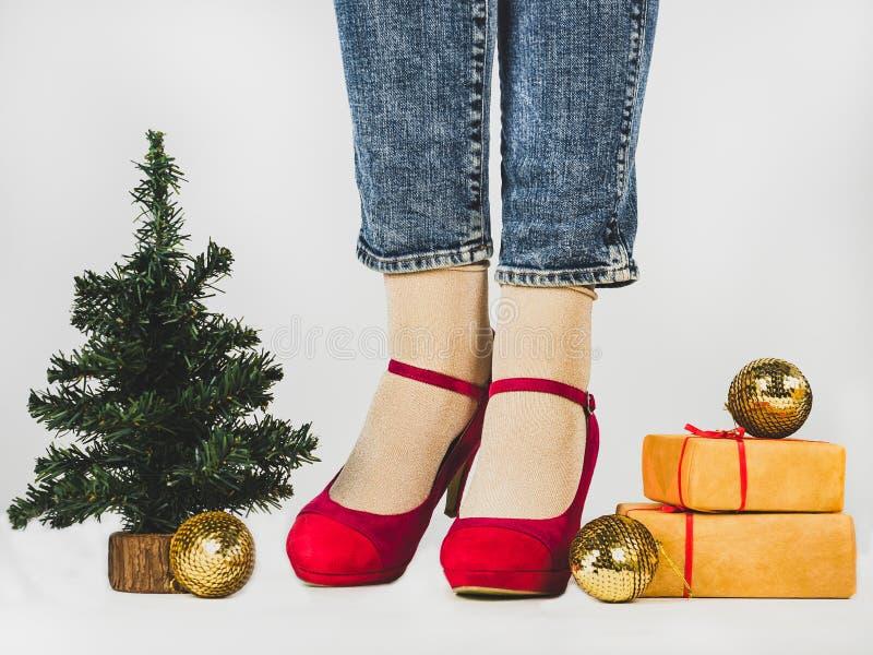 Ноги женщин, стильные ботинки, подарки с красной лентой стоковая фотография rf