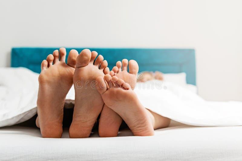 Ноги закрывают вверх молодых любящих пар наслаждаясь на кровати стоковые изображения